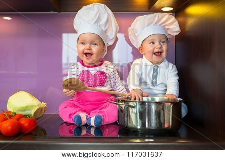 Little twins, boy and girl in chef hat cooking at the kitchen