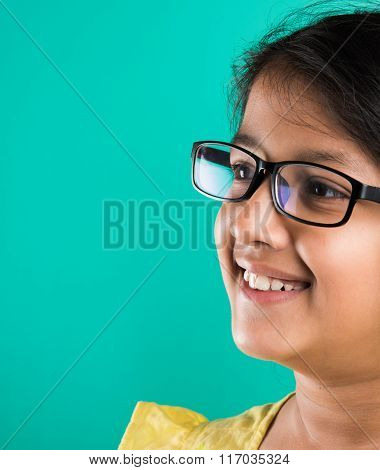 Happy little indian girl smiling while wearing glasses, green background, indian small girl wearing