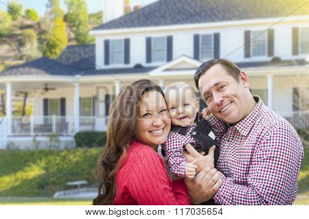 Happy Young Family With Baby Outdoors In Front of Beautiful Custom Home.