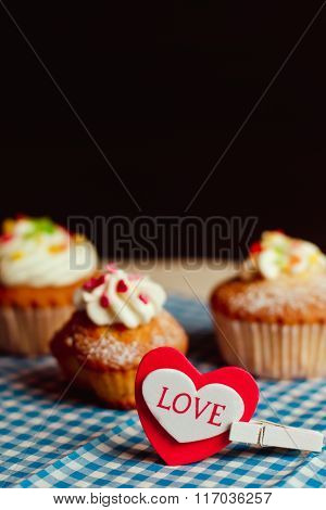 Beautiful Cupcakes And A Heart With The Inscription Love Lie On A Vintage Checkered Tablecloth