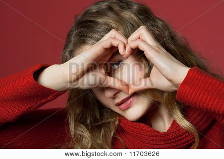 Young Woman Looking Through Heart