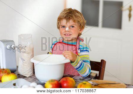 Funny blond kid boy baking apple cake indoors