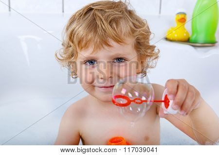 toddler boy playing with soap bubbles in bathtub