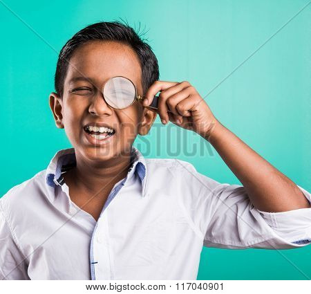 happy indian kid with magnifying glass, asian boy looking through magnifying glass with smile, india