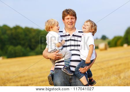 Young father and two little twins boys having fun on yellow hay