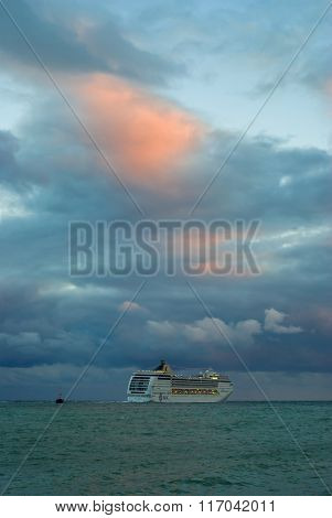 Big oceanic ship sailing off from Yalta port at fall evening