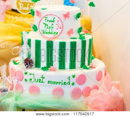 Delicious wedding cake in white , green and pink