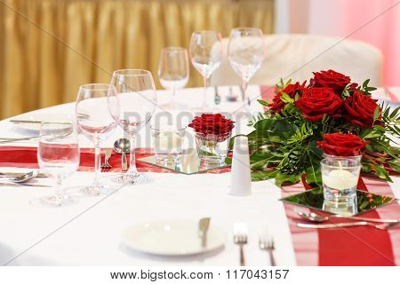 Elegant table set in red and white for wedding or event party.