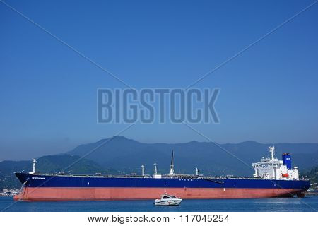Oil tanker and a coast guard vessel in Batumi oil terminal on a sunny summer day.