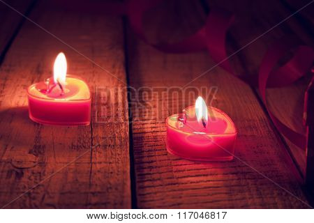 Red Burning Heart Shaped Candles On Rustic Wooden Table. Valentine's Day And Mother's Day Background