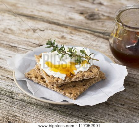 Snack gluten free crispbread with cream cheese honey and thyme on a simple ceramic dish on the kitchen table for a healthy family breakfast. selective Focus