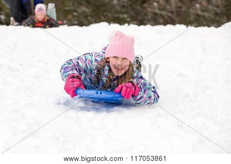 Girl Sledding Head First And Looking At Camera
