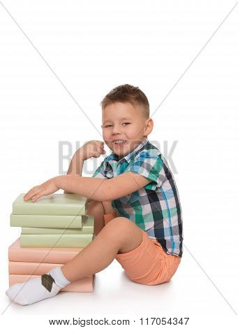 child hugs a stack of books