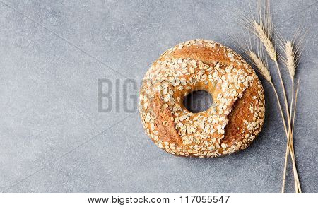 Wholegrain rustic bread with seeds on stone dark background