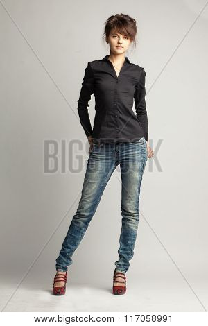 Full Height Portrait Of Young Brunette Woman In Black Shirt And Jeans