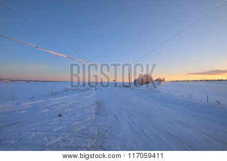 Snowcovered Rural Highway During Winter Sunset