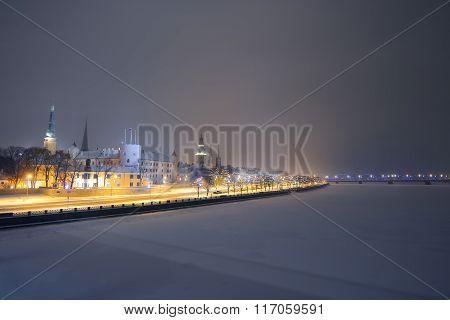 Panorama Of Night Riga In Winter With Daugava River Frozen