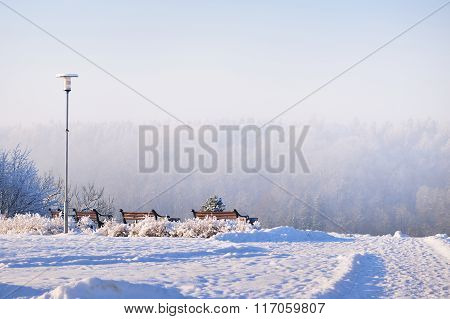 Benches And A Lamppost Facing A Snowy Panorama Of Gauja River In Sigulda