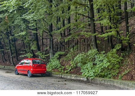 Picturesque road with red car at Balkan mountain in rainy day