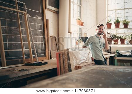 Positive business owner on phone in his workshop