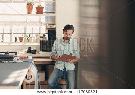 Independent designer businessman checking orders on his clipboar