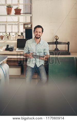 Designer businessman in his studio using a digital tablet