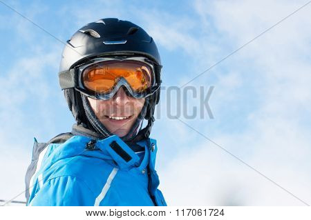 Smiling man in the blue skiing jacket, helmet and glasses against cloudy sky