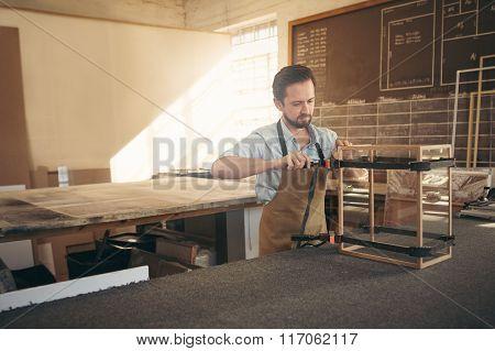 Skilled craftsman manufacturing a display case in wood worksho