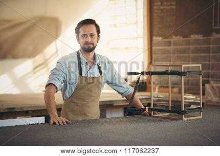 Carpenter standing proudly alongside a display case he is making
