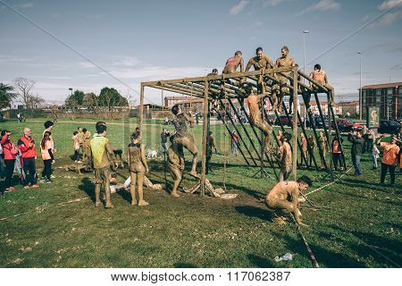 Runners climbing structure in a test of extreme obstacle race