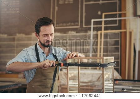 Carpenter making a display case with skill and care