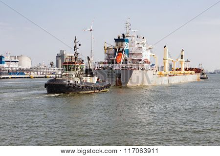 Tugboat With Cargo Ship In The Harbor Of Antwerp, Belgium