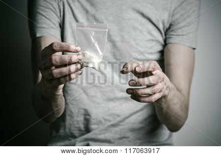 The Fight Against Drugs And Drug Addiction Topic: Addict Holding Package Of Cocaine In A Gray T-shir
