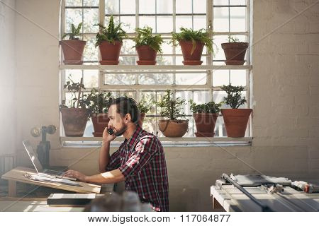 Designer entrepreneur using his phone while working on lapto