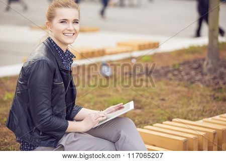 Smiling Young Womanrelaxing With Tablet On Fresh Air