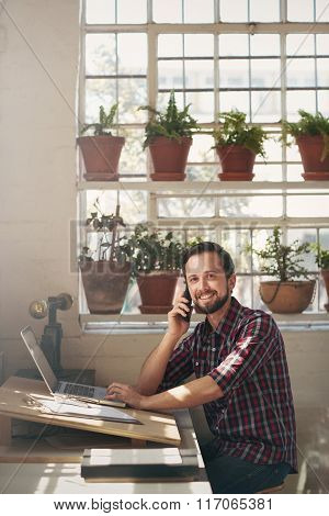 Entrepreneur smiling at the camera from his studio office space