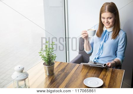 Woman Reading Magazine And Drinking Cappuccino In Coffee Shop