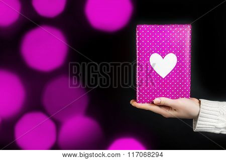 Hand holding pink gift isolated on black