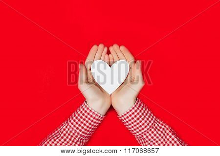 woman holding white heart on red