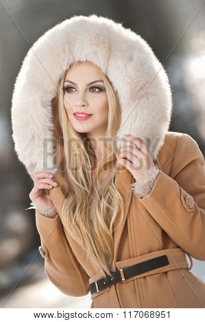 Attractive young Caucasian adult with light brown fur coat hood. Beautiful blonde girl