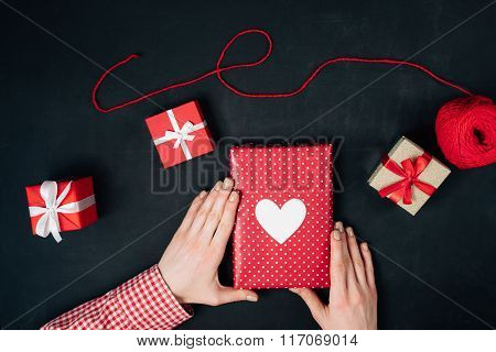 Female hands are holding a christmas gift on black
