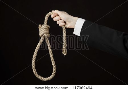 Suicide And Business Topic: Hand Of A Businessman In A Black Jacket Holding A Loop Of Rope For Hangi