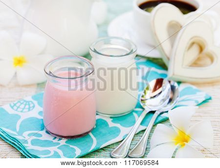 Homemade yogurt strawberry and vanilla in glass jars Romantic breakfast background with wooden heart