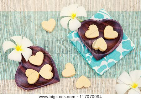 Handmade heart shape cookies on wooden plate and blue napkin Outdoor background Frangipani flower To