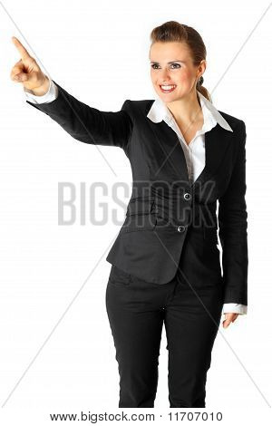 Full length portrait of smiling modern business woman touching abstract screen isolated on white