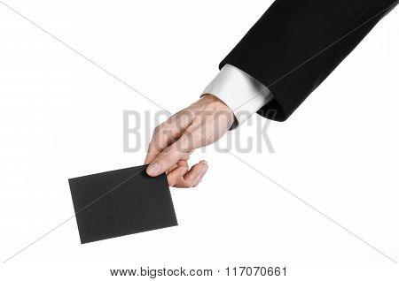 Business And Advertising Topic: Man In Black Suit Holding A Black Blank Card In Hand Isolated On Whi