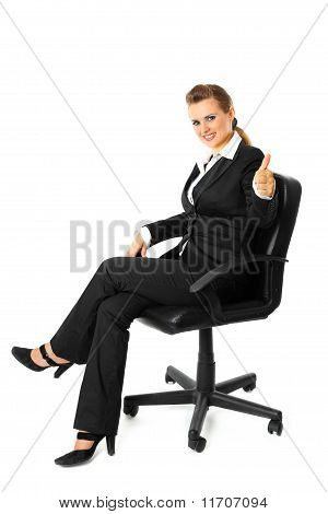 Smiling modern business woman sitting on chair and showing thumbs up gesture isolated on white