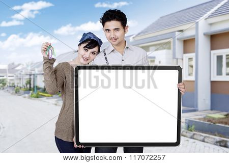 Couple With Billboard And Keys Of New House