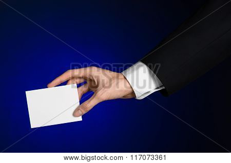 Business And Advertising Topic: Man In Black Suit Holding A White Blank Card In His Hand On A Dark B