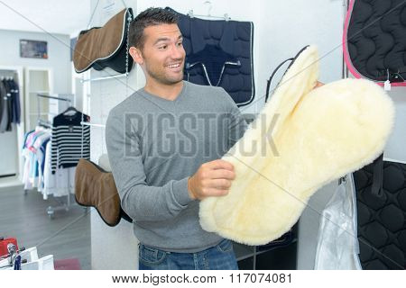 Man with surprised expression holding horse blanket